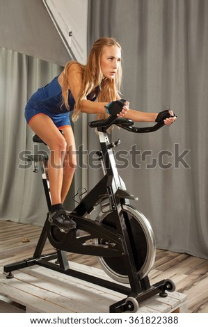 Young beautiful woman doing exercise on a spinning machine in a cycling gym. - stock photo