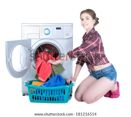 Young beautiful woman doing laundry in the washing machine. Isolated on white background