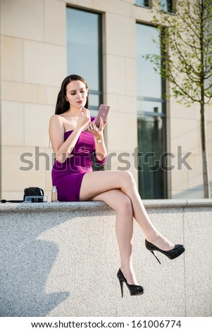 Young beautiful woman doing make-up on street with buildings in background - stock photo