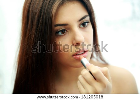 Young beautiful woman doing makeup  - stock photo