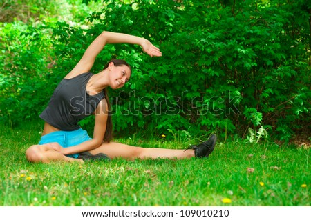 Young beautiful woman doing sports stretching exercise on green grass at park