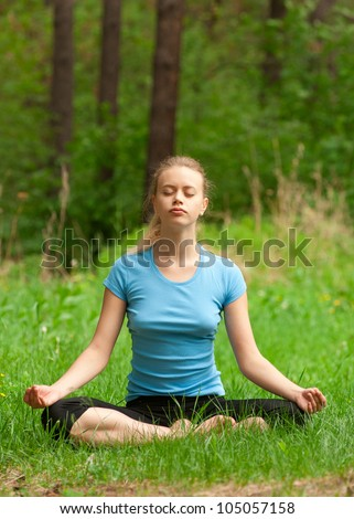 Young beautiful woman doing yoga meditation in forest outdoors - stock photo