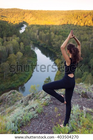 young beautiful woman doing yoga outdoors - stock photo