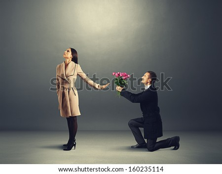 young beautiful woman don't looking at man with flowers - stock photo