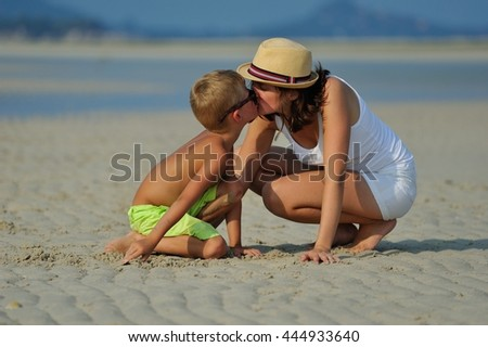 Young beautiful woman dressed in white with a hat crouched in the sand beside her son they interact lovingly and tenderness looking at each other - stock photo