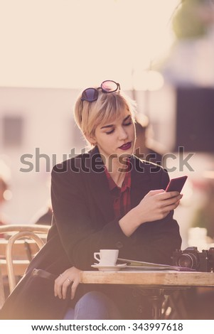 Young beautiful woman drinking coffee and using her mobile phone  - stock photo