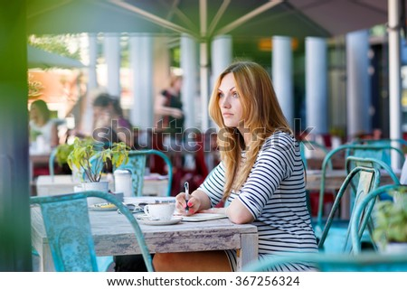 Young beautiful woman drinking coffee and writing diary, book or notes in an outdoor cafe in Berlin, Germany. - stock photo