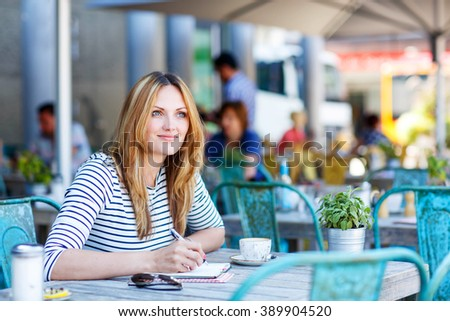 Young beautiful woman drinking coffee and writing diary, book or notes in an outdoor cafe in Europe, London city. - stock photo
