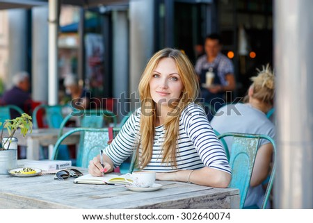 Young beautiful woman drinking coffee and writing diary, book or notes in an outdoor cafe in Paris, France. - stock photo