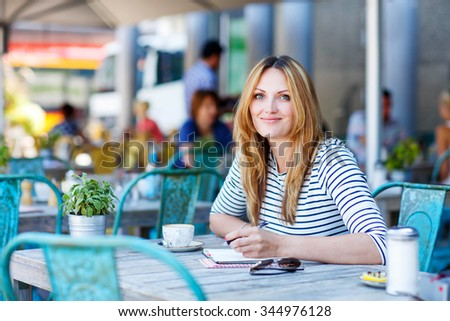 Young beautiful woman drinking coffee and writing diary, book or notes in an outdoor cafe in Paris, France - stock photo