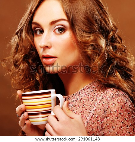 young beautiful woman drinking coffee over beige background - stock photo