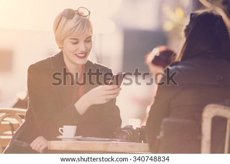 Young beautiful woman drinking coffee with her friend  at cafe, and using her mobile phone  - stock photo