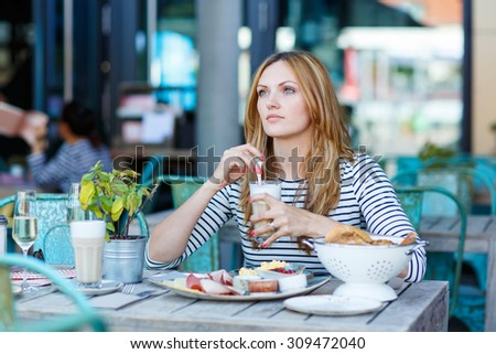 Young beautiful woman drinking coffee with milk and having healthy breakfast in outdoor cafe in summer city in Europe. - stock photo