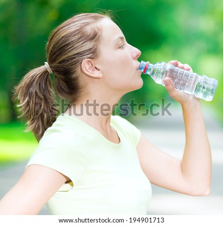 Young beautiful woman drinking cold mineral water from a bottle  after sport fitness exercise at green summer park