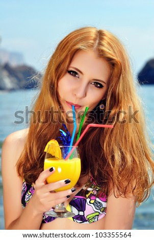 Young beautiful woman drinking fresh orange juice cocktail on the beach