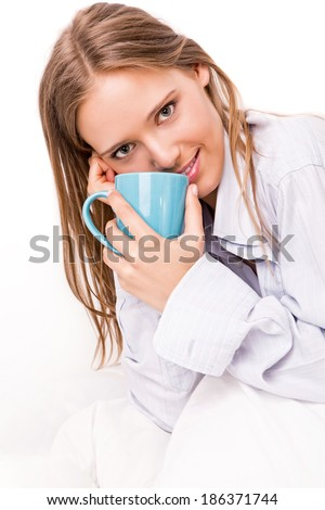 Young beautiful woman drinking something in bed