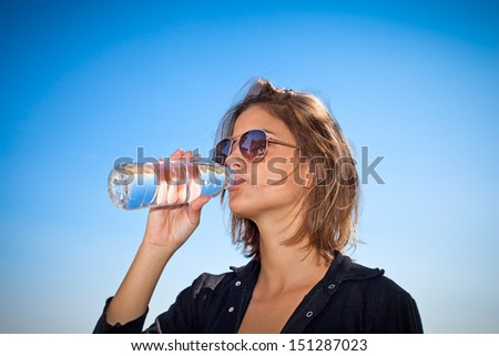 Young beautiful woman drinking water at summer
