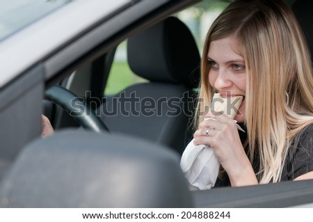 Young beautiful woman driving car and eating fast food - portrait through side window - stock photo