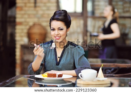 Young beautiful woman eating a dessert - stock photo