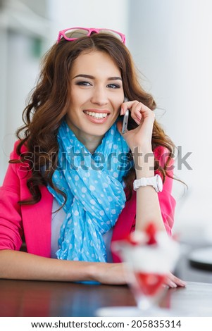 young beautiful woman eating a dessert and talking on the phone. Spending time at the restaurant. Attractive young woman drinking coffee at the restaurant and talking on the phone - stock photo