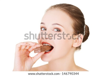 Young beautiful woman eating bar, isolated on white - stock photo