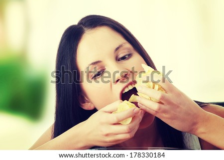 Young beautiful woman eating chips