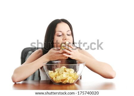Young beautiful woman eating chips, isolated on white