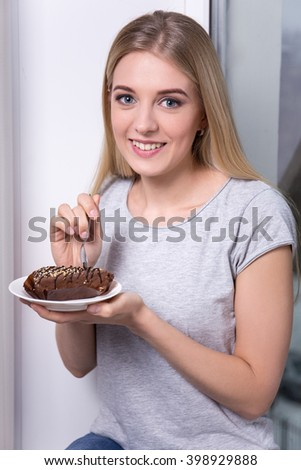 young beautiful woman eating chocolate cake at home - stock photo