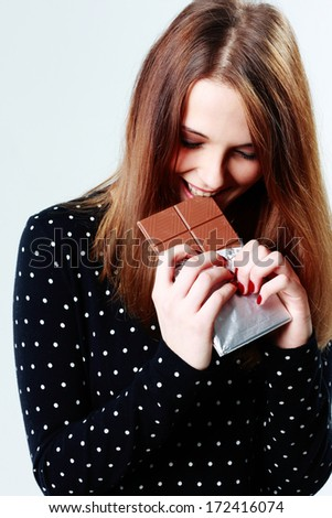 Young beautiful woman eating chocolate on gray background - stock photo