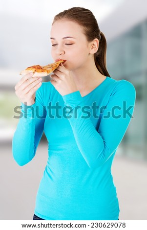 Young beautiful woman eating pizza - stock photo