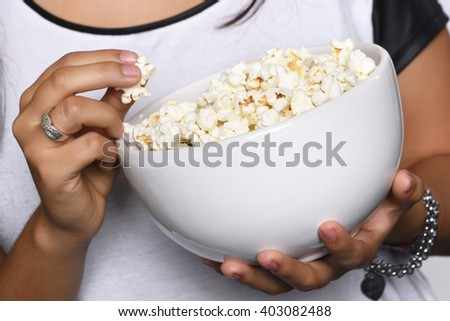 Young beautiful woman eating popcorn. Isolated white background - stock photo