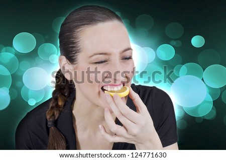 Young beautiful woman eating sour lemon - stock photo