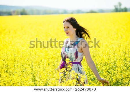 Young beautiful woman enjoying life in blossoming rapeseed field - stock photo