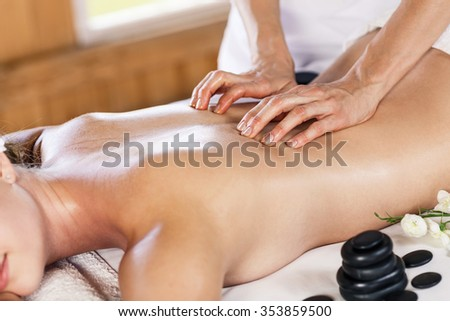 Young beautiful woman enjoying massage on the table at spa center - stock photo