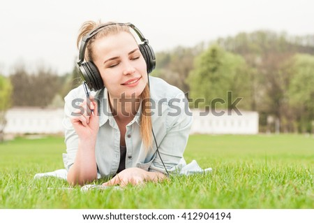 Young beautiful woman enjoying music outdoors on headphones lying on grass and looking happy - stock photo