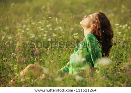 Young beautiful woman enjoying nature in the flowers field