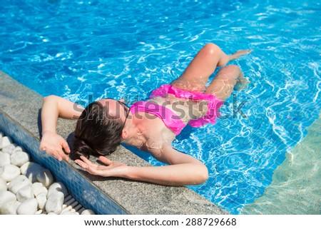 Young beautiful woman enjoying summer vacation in luxury swimming pool - stock photo