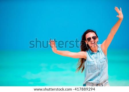 Young beautiful woman enjoying the music on the beach - stock photo
