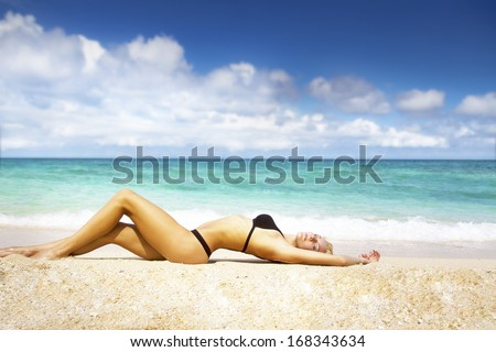young beautiful woman enjoying vacation laying on sand beach on tropical sea background