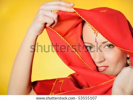 Young beautiful woman eyes in indian traditional jewellary, bindi , sari dress and makeup. yellow background - stock photo