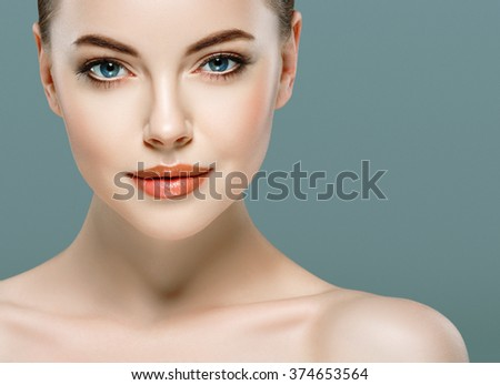 Young beautiful woman face portrait with healthy skin on gray background  - stock photo