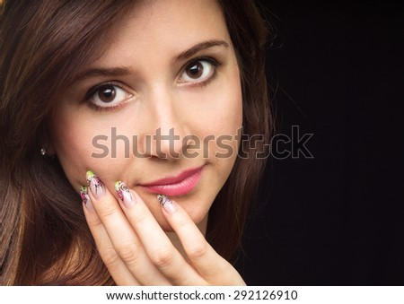 Young beautiful woman fashion portrait on black background. Pretty caucasian girl with make-up, manicured nails and clean skin - stock photo