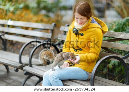 Young beautiful woman feeding a squirrel in Madison Square Park, New York