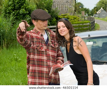 Young, beautiful woman getting directions from a local farmer - stock photo