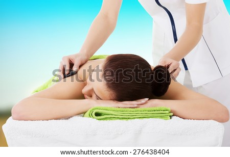Young beautiful woman getting stone massage in spa. - stock photo