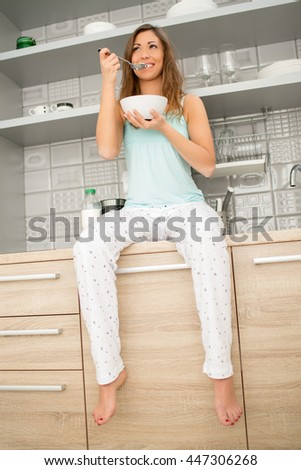 Young beautiful woman having a breakfast in kitchen and enjoying a sunny morning.