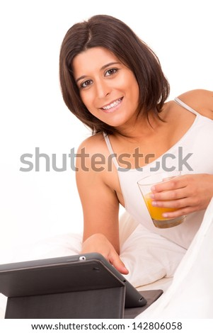 Young beautiful woman having breakfast in bed while working or relaxing with her computer