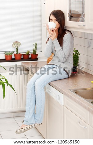 Young beautiful woman having coffee or tea in the kitchen