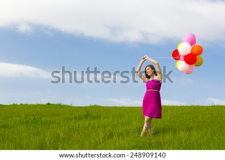 Young beautiful woman having fun with balloons on a green meadow - stock photo
