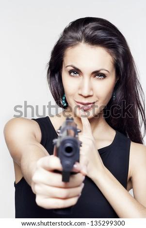 Young beautiful woman holding a gun saying shh - stock photo